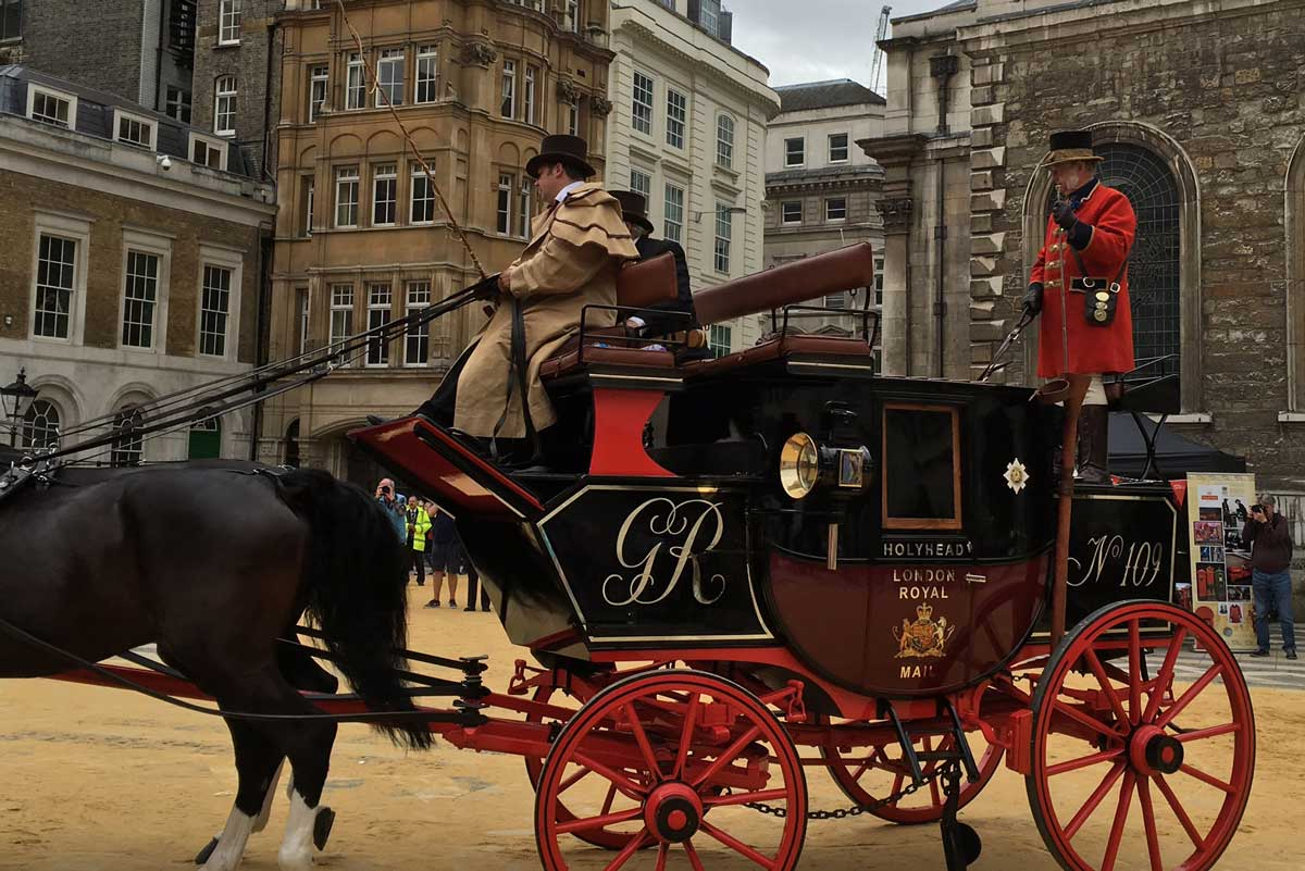 A horse-drawn Mail Coach enters the Guildhall courtyard