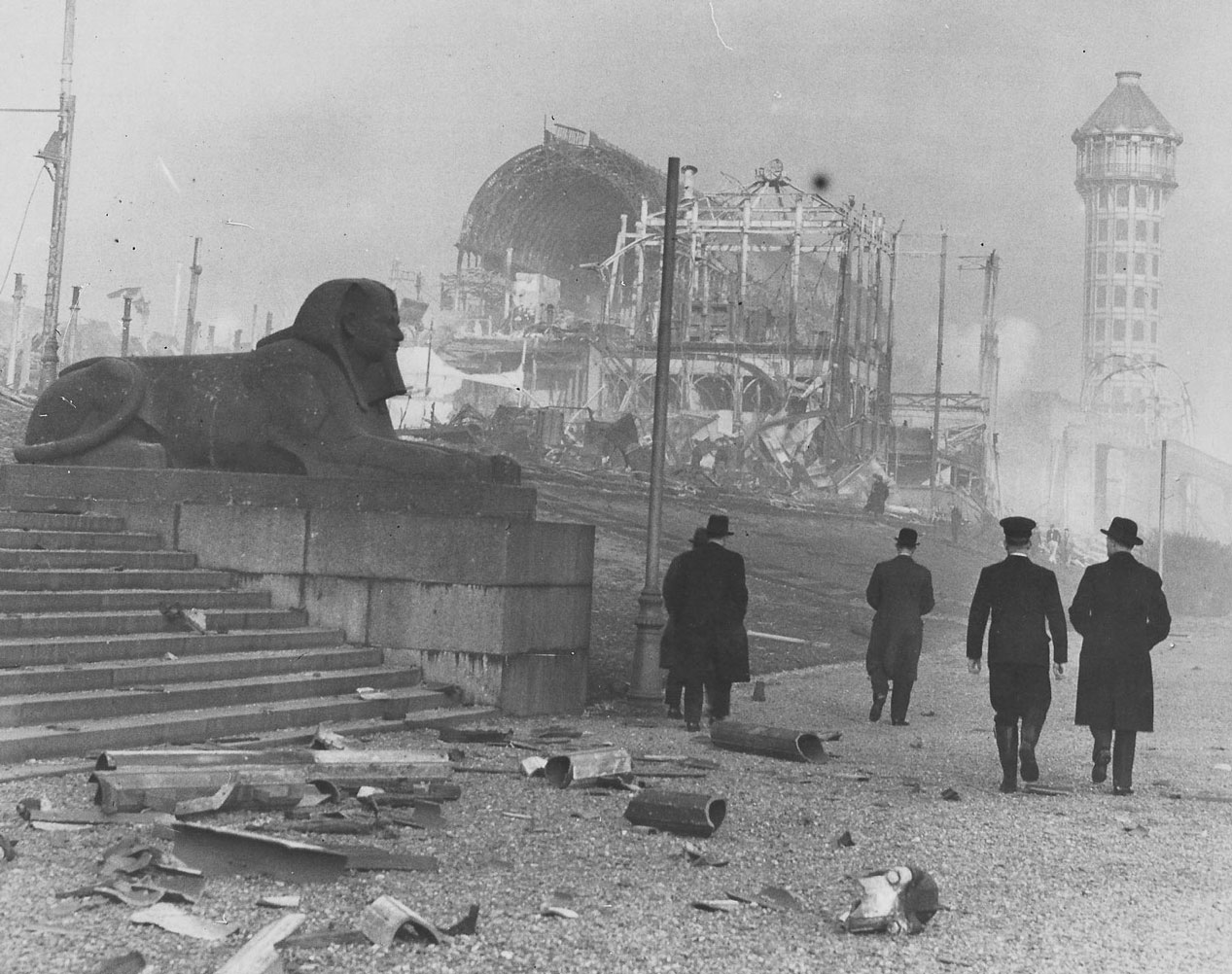 Men walking towards the burnt out Crystal Palace.