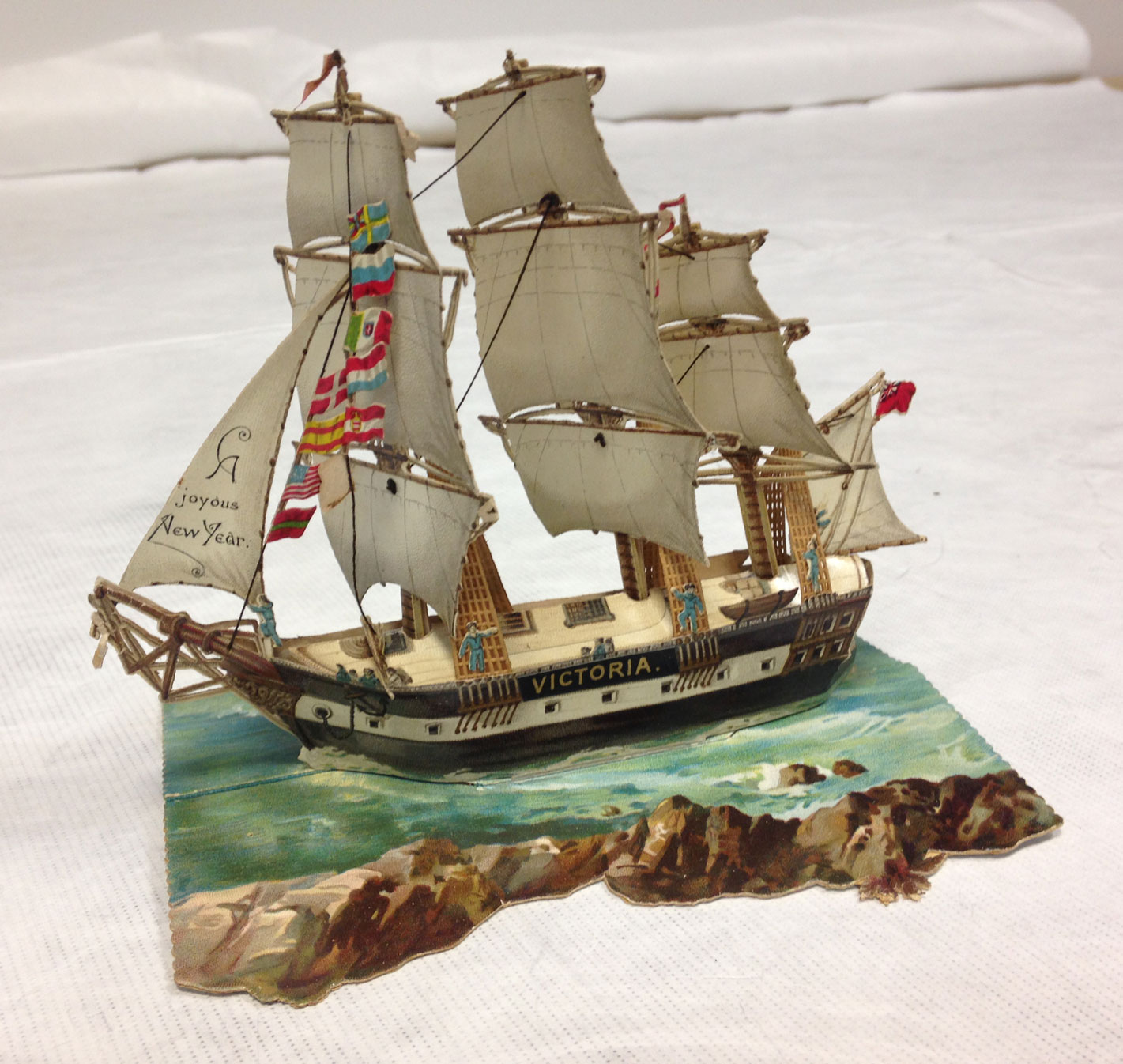 Pop-up New Year card of a galleon ship called 'Victoria' on the sea.