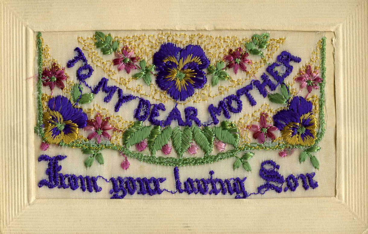An embroidered card decorated with flowers and the words, To my Dear Mother from your loving Son