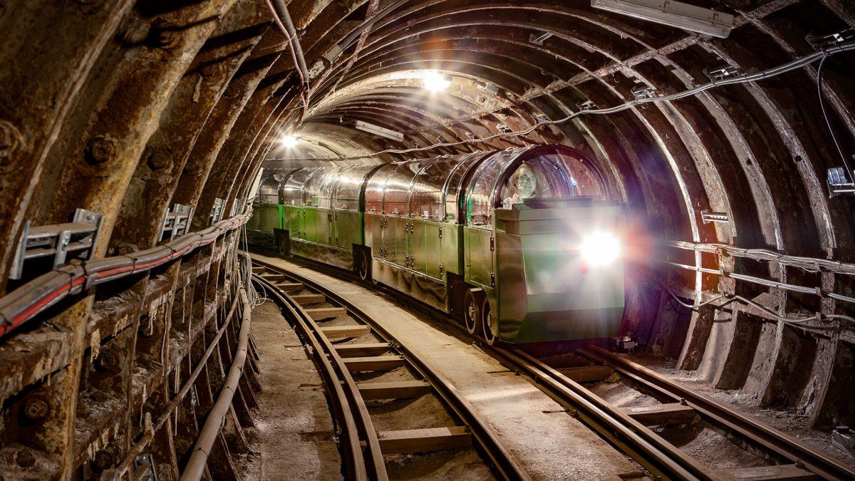 Green train coming down Mail Rail tunnel