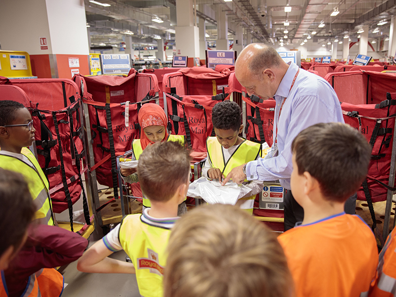 Group of school children in the Mount Pleasant Sorting Office in Central London looking at a piece of post with a Royal Mail staff member.