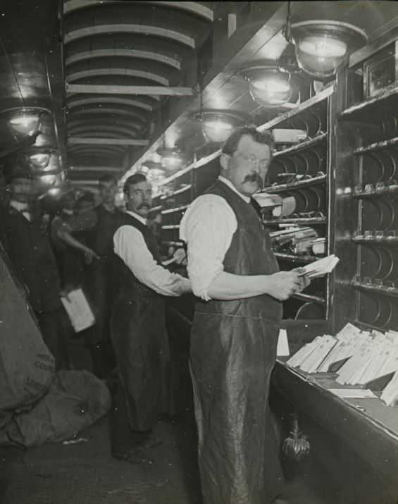 Men standing in front of sorting frames sorting mail, photographic lantern slide, early 20th Century