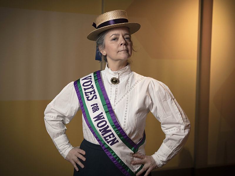 An actor wearing a Votes for Women suffragette sash.