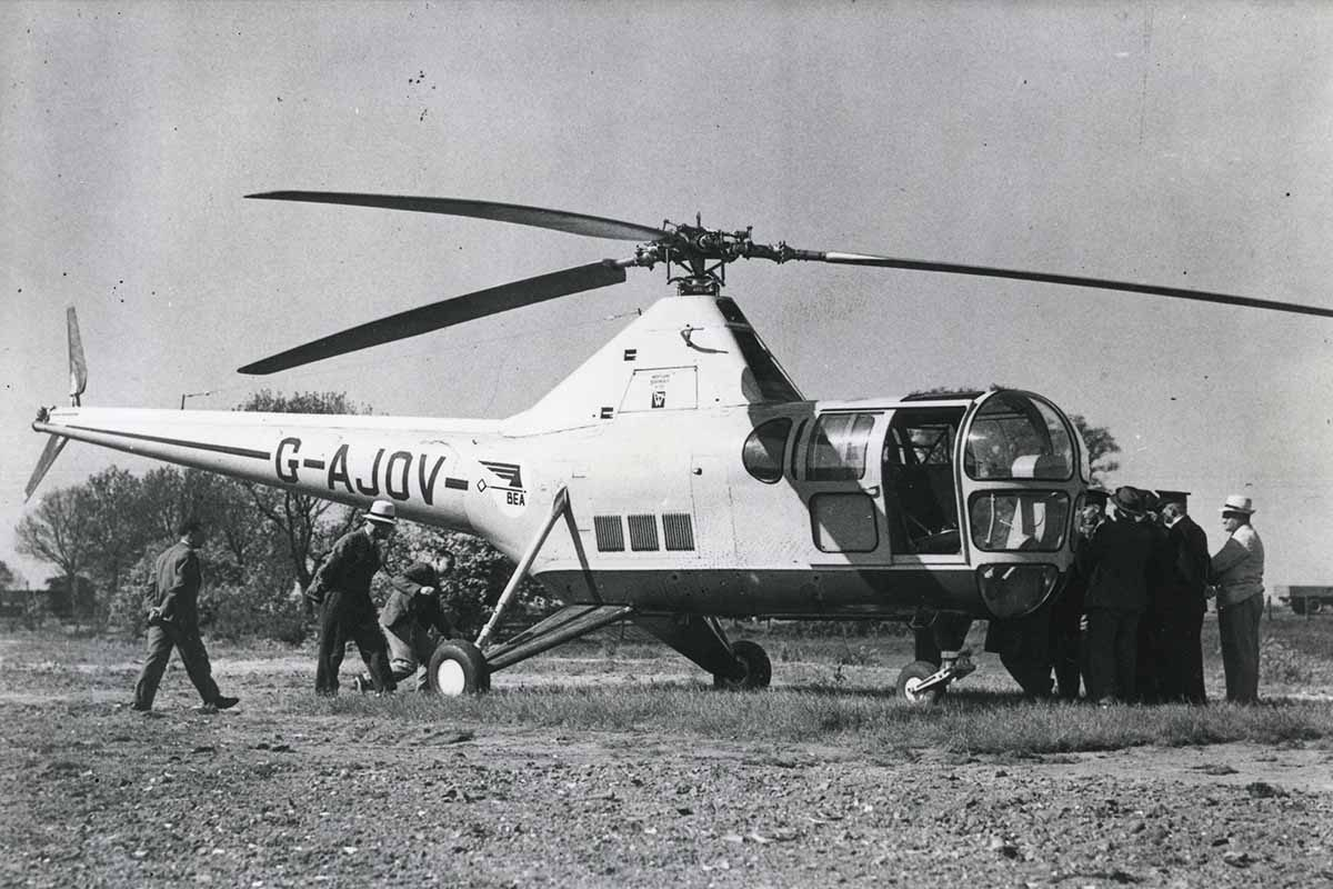 A black and white photo of a Helicopter mail trial in Norfolk. Postal staff surround a helicopter.