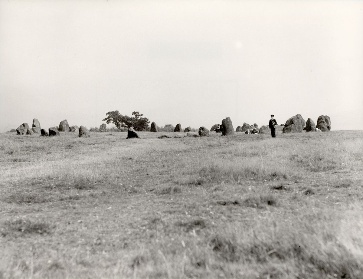 Black and white photograph of a postman at Castlerigg Stone Circle.