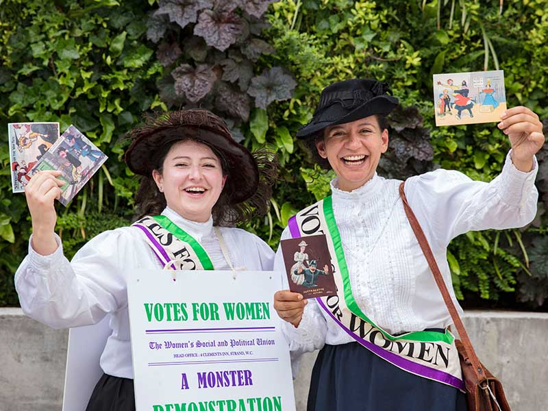 Learn about the suffragettes this October at The Postal Museum. Photo of 2 actors playing suffragettes in the courtyard of the museum.