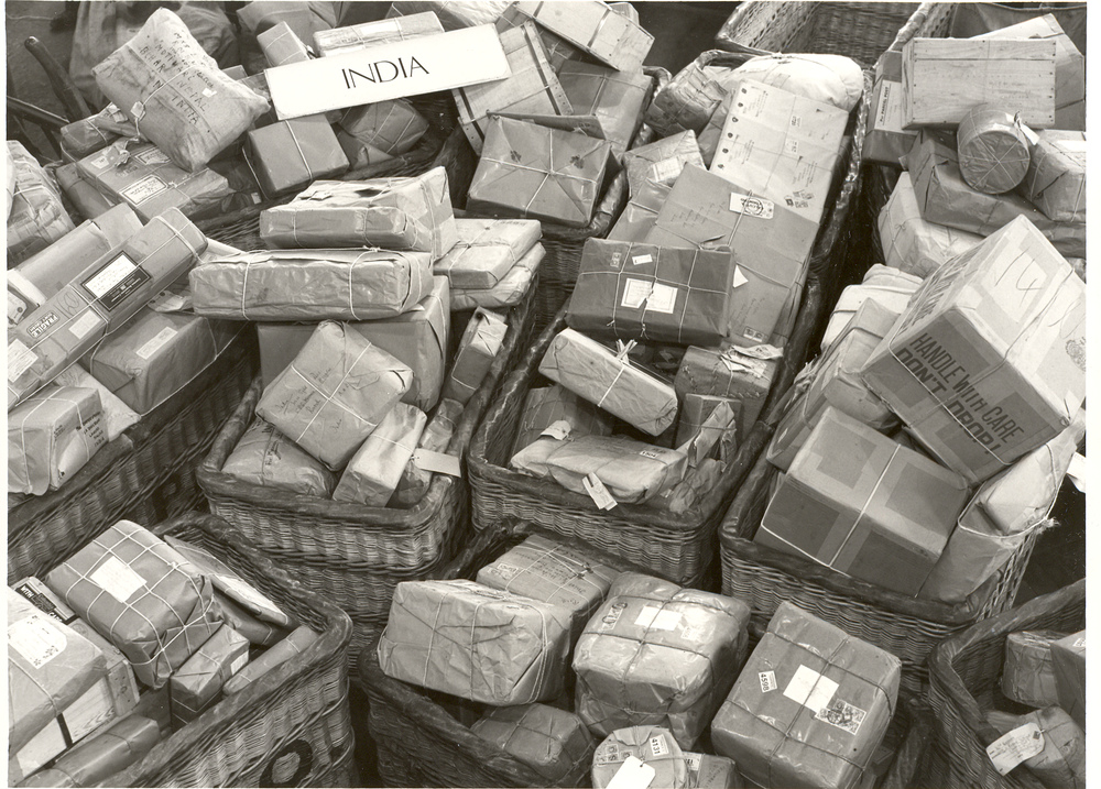 Black and white photograph of numerous parcels ready to be transported to India.