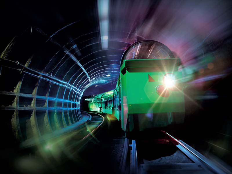 A photograph of a green miniature Mail Rail train travelling through an underground tunnel.