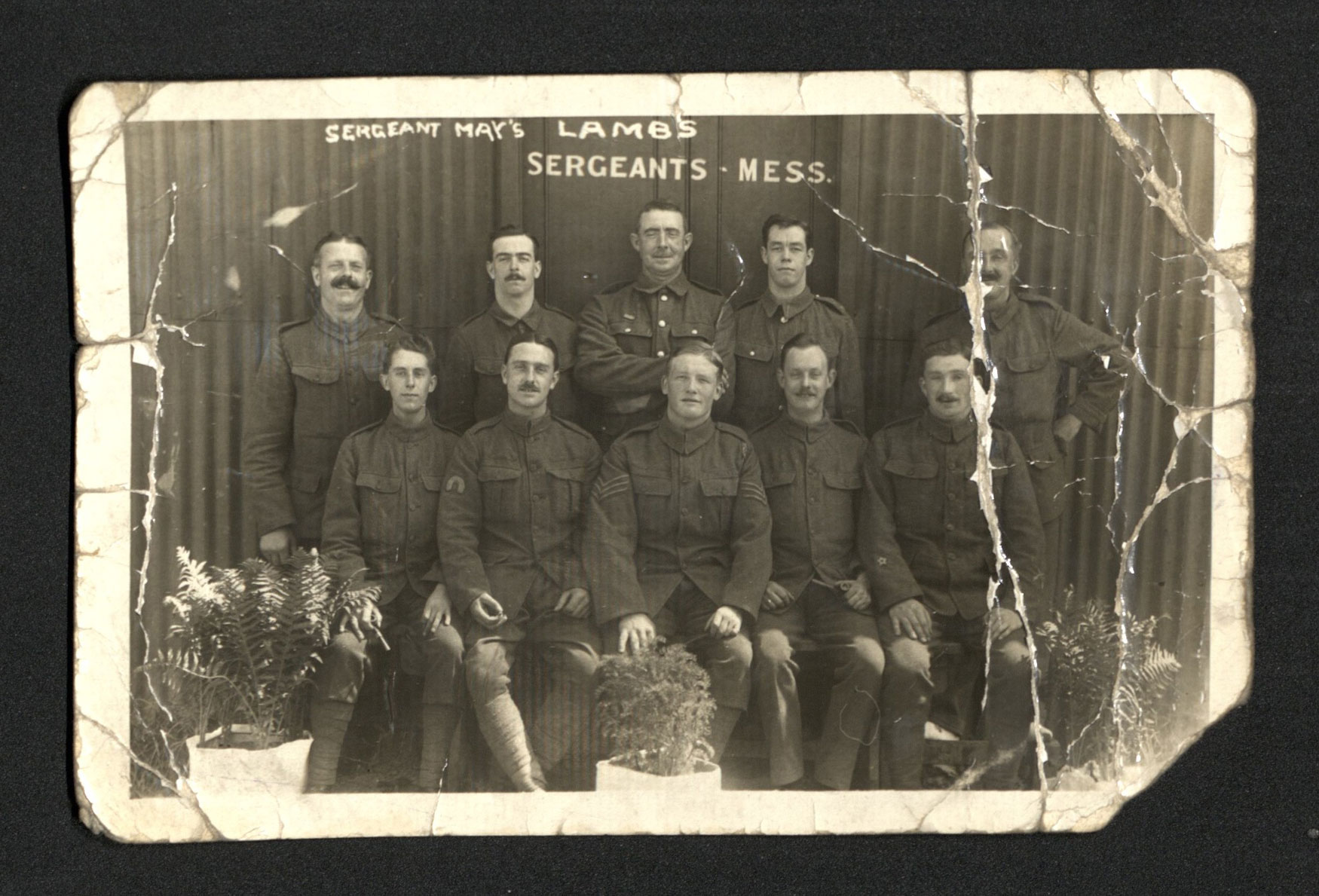 A posed photograph of soldiers in front of the sergeants mess.