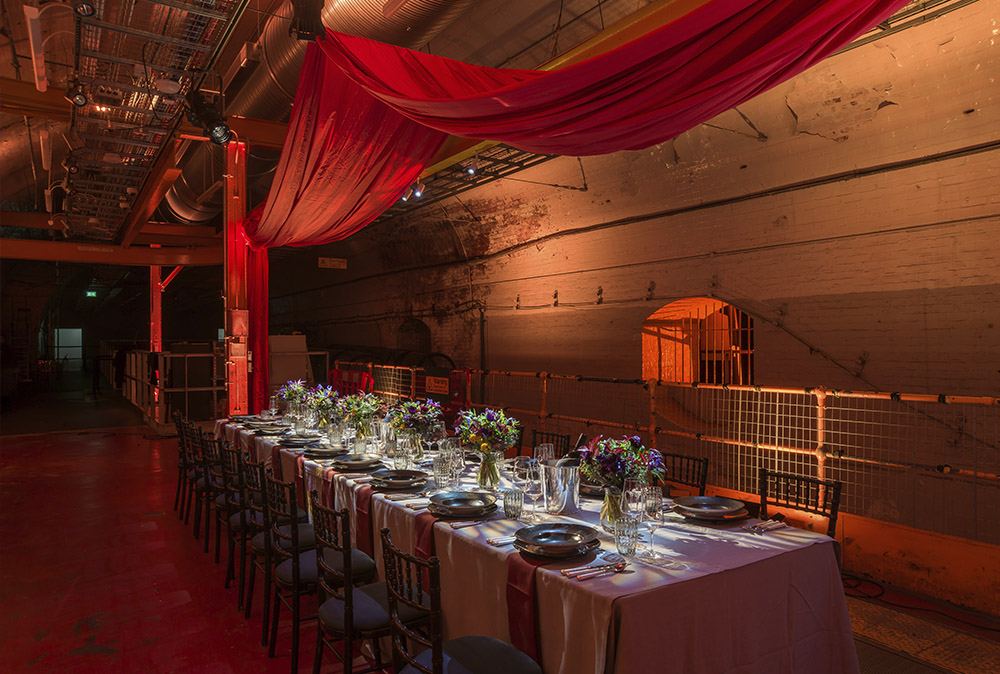 An event table set up in the Mail Rail venue space with lighting and decor.