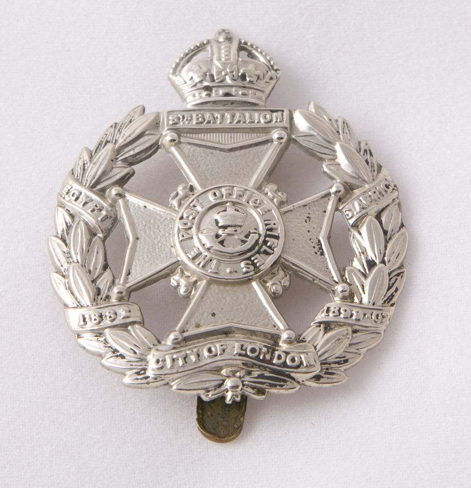 A silver metal badge for the Post Office Rifles consisting of a central cross circled by a laurel wreath.