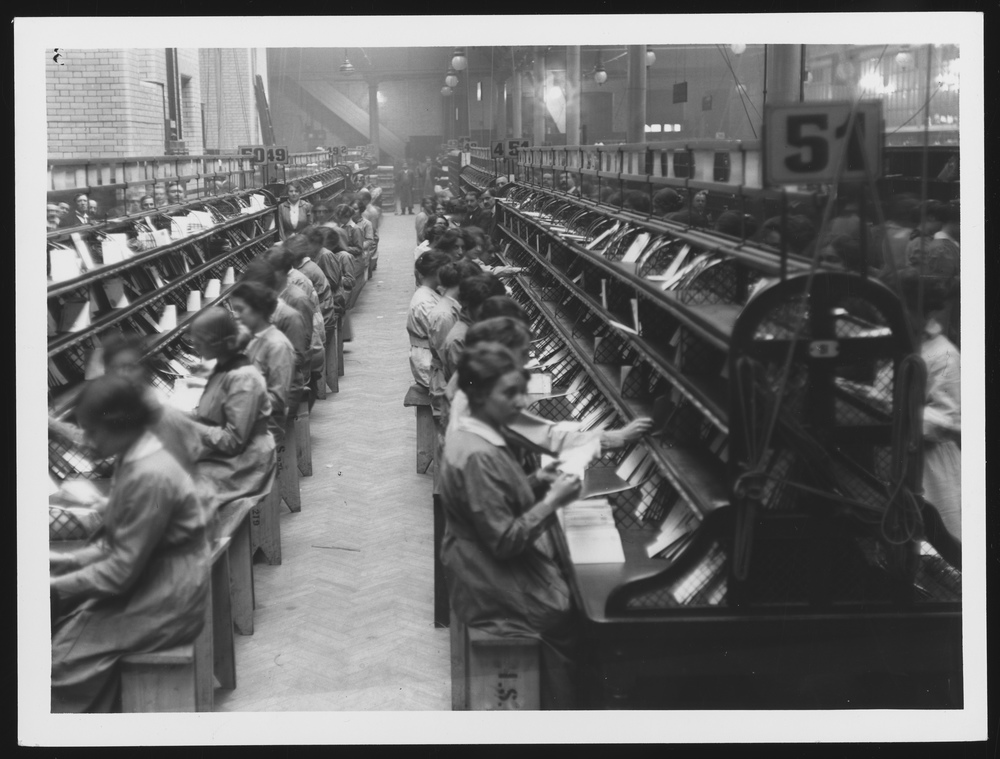 Photograph of numerous women sat in rows sorting letters.