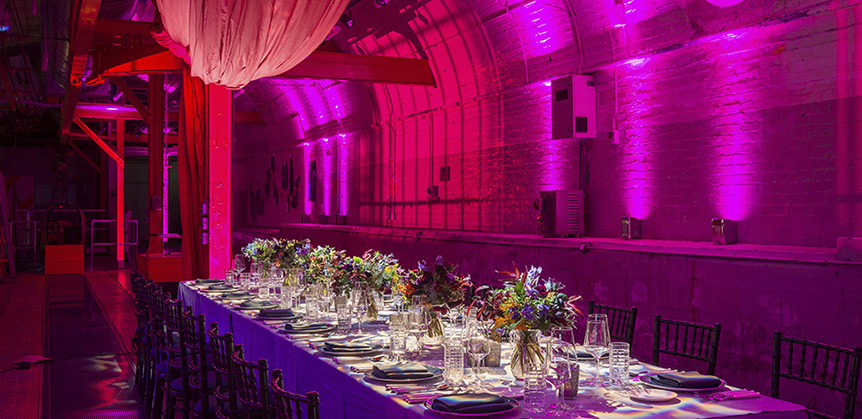 An event table set up in the Mail Rail venue space with purple lighting and decor.