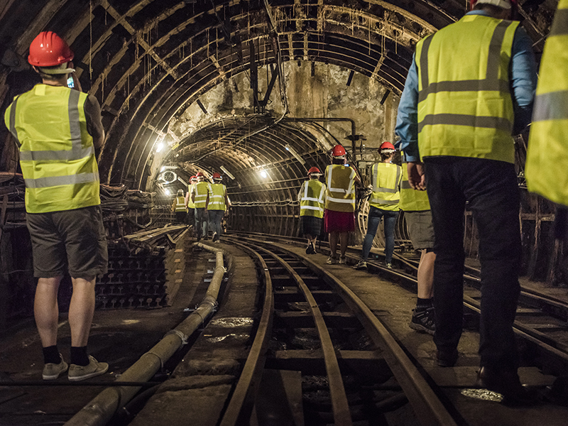 Photo of a group walk through the abandoned underground tunnels of London's old Post Office Railway.