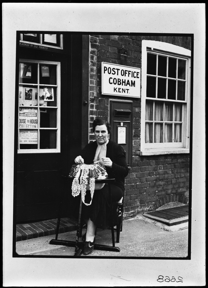 Black and white photograph of a women sat outside of Cobham Post Office making lace.