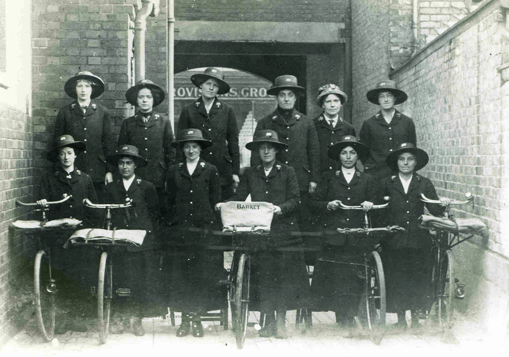Black and white photograph of Barnet postwomen standing next to bicycles.