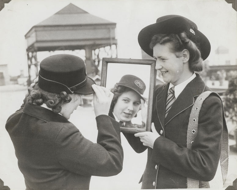 Black and white photograph of a women adjusting her postwomen hat in a mirror.