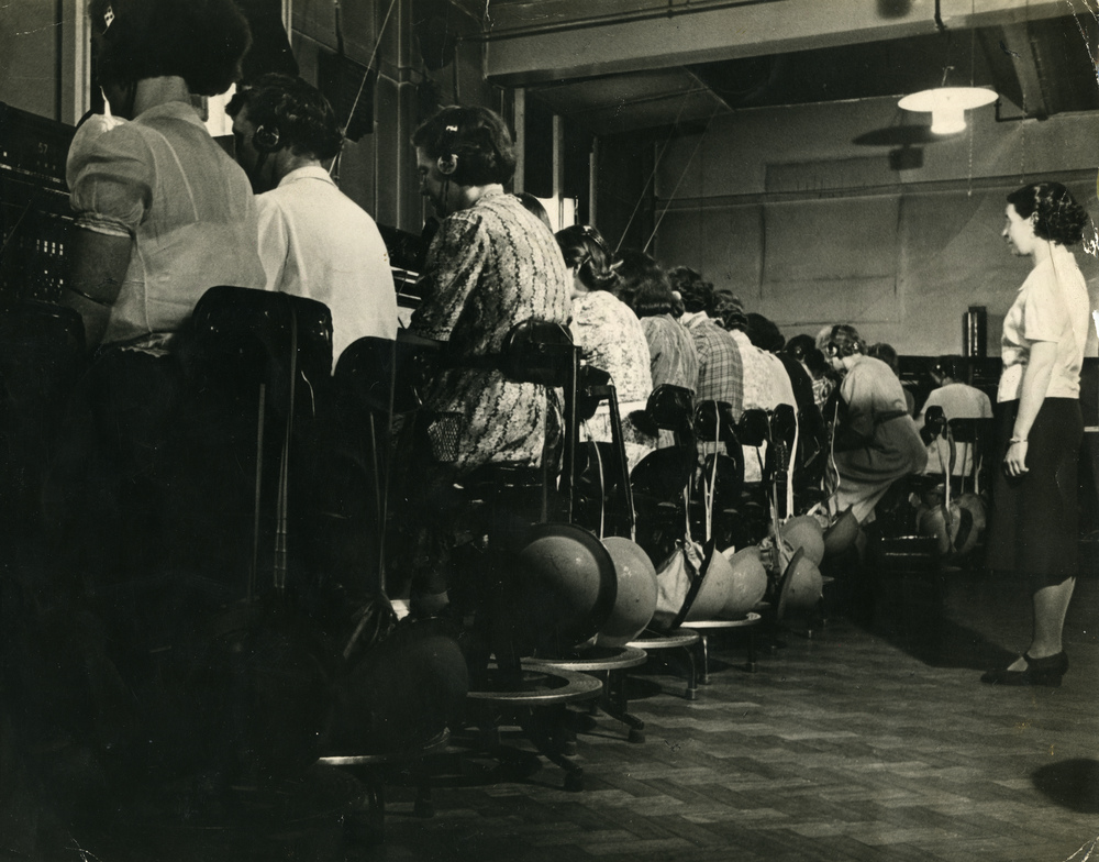 Black and white photograph of women sat in a line working the telephone exchange with a supervisor.
