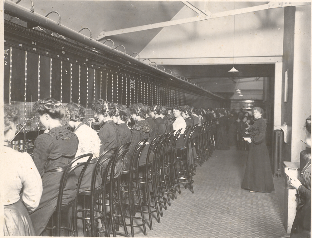 A black and white image of women working at a telephone switchboard.