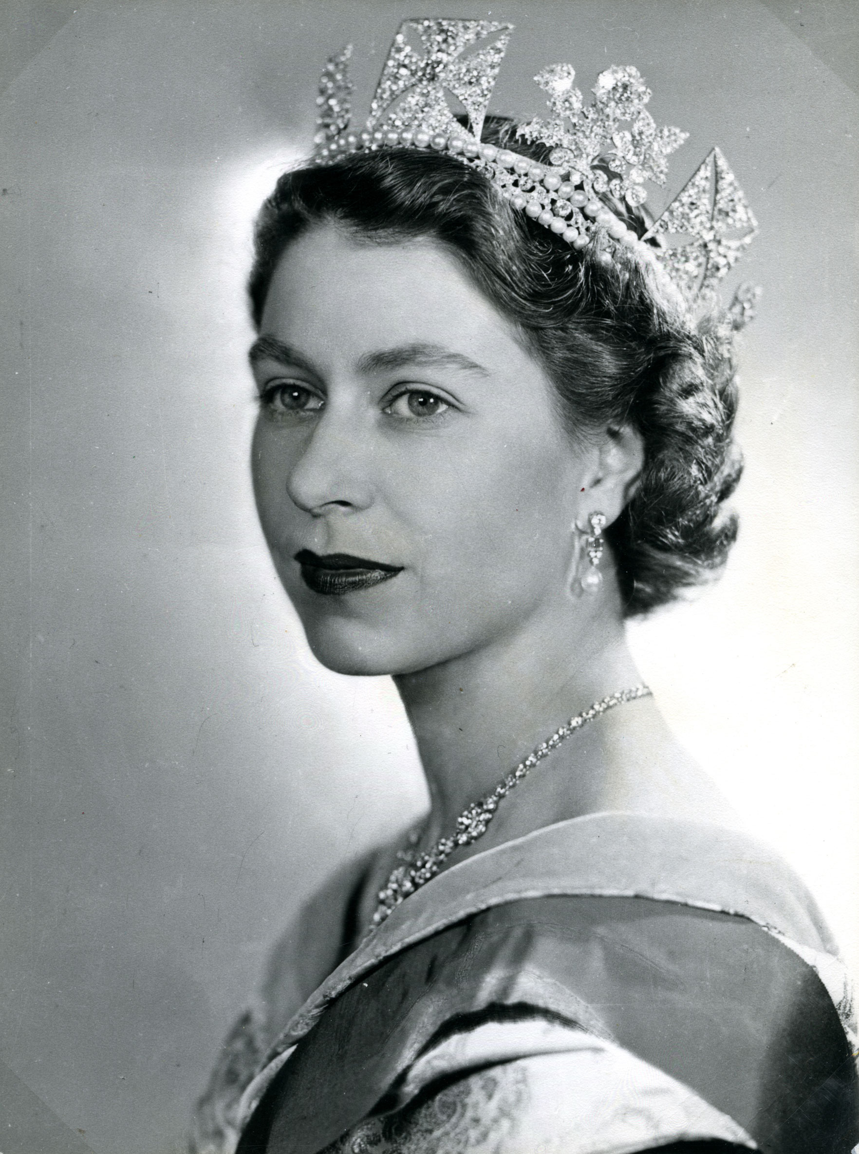 Black and white image of the Queen in three-quarter pose wearing a crown.