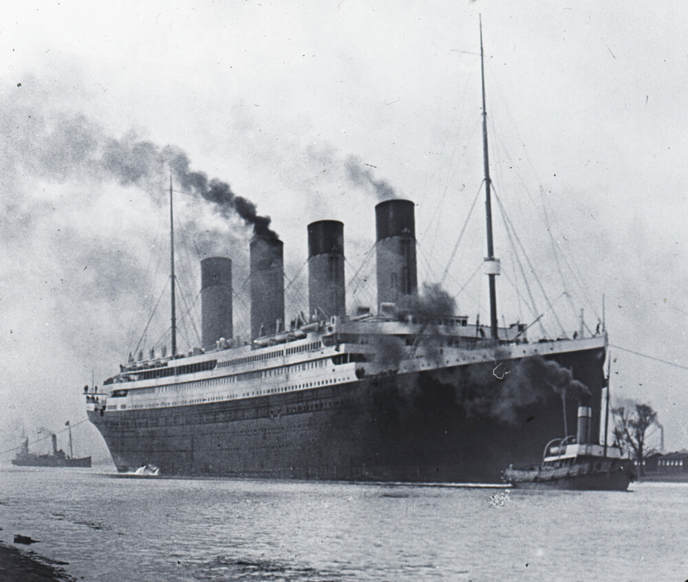 A black and white photographic image showing the 'Titanic' leaving dock with two small boats before and behind her. Smoke is coming out of all the ships funnels.
