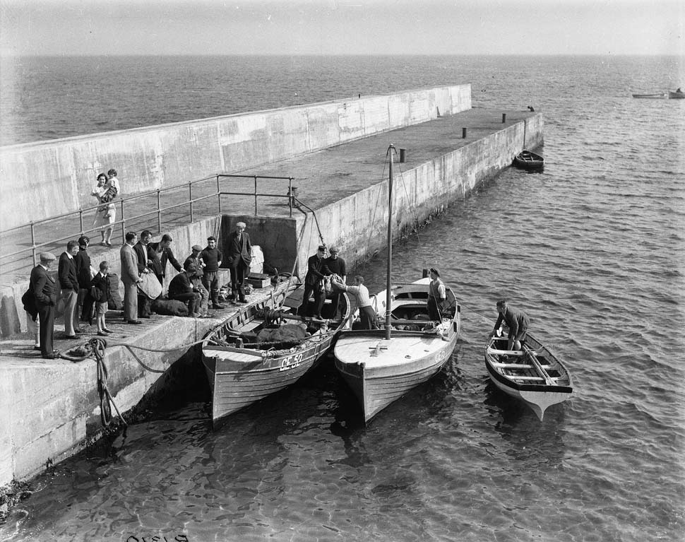A black and white photograph showing mail being loaded from a pier onto a one masted sailing boat.