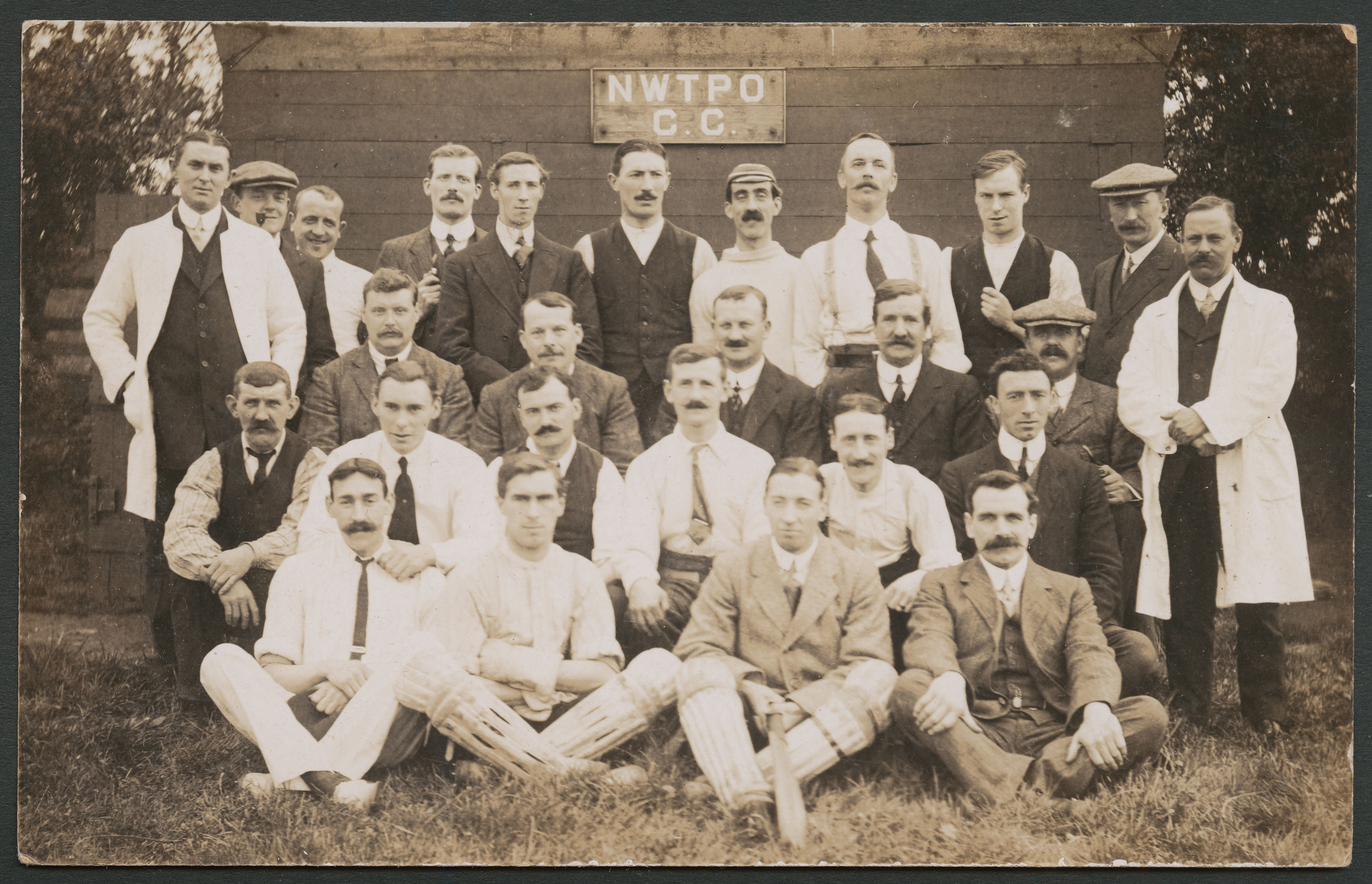 Black and white photograph of a all male Post Office cricket team grouped for a team photograph.