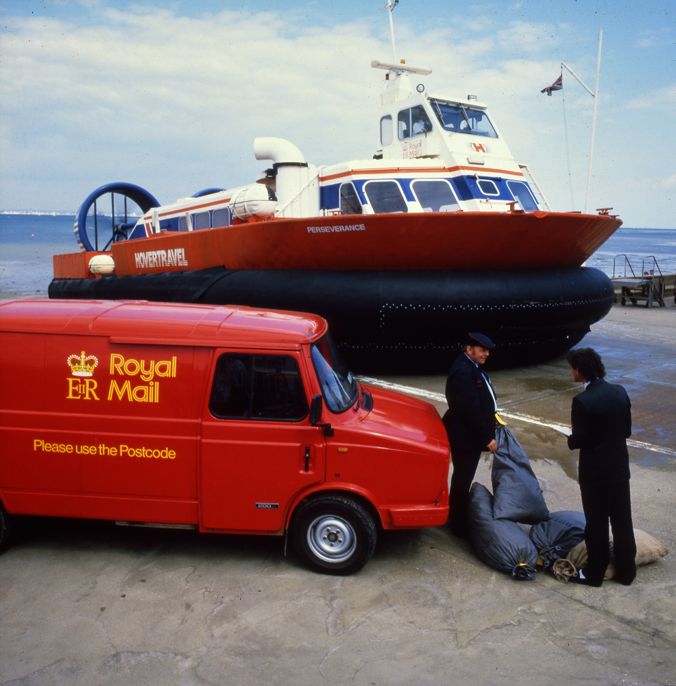 A colour photograph showing a hovercraft on the slipway. A Royal Mail van and two postmen with a mail bag are in the foreground.