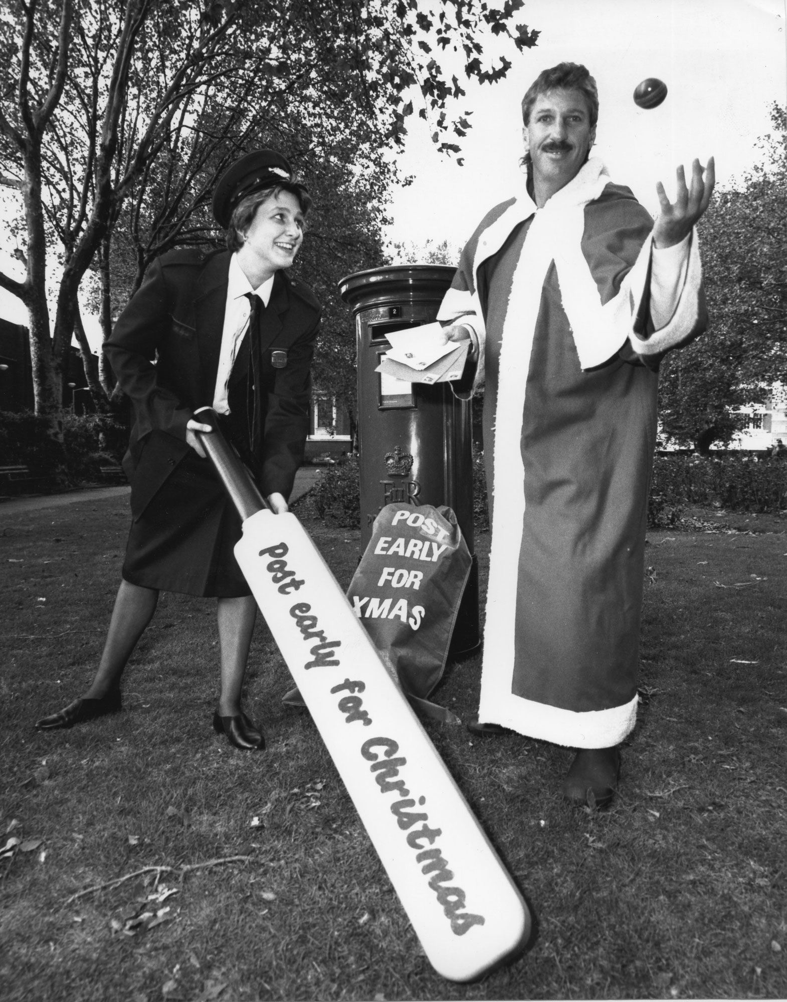 A black and white photograph with a postwomen holding a large cricket bat and Ian Botham dresses as Santa.