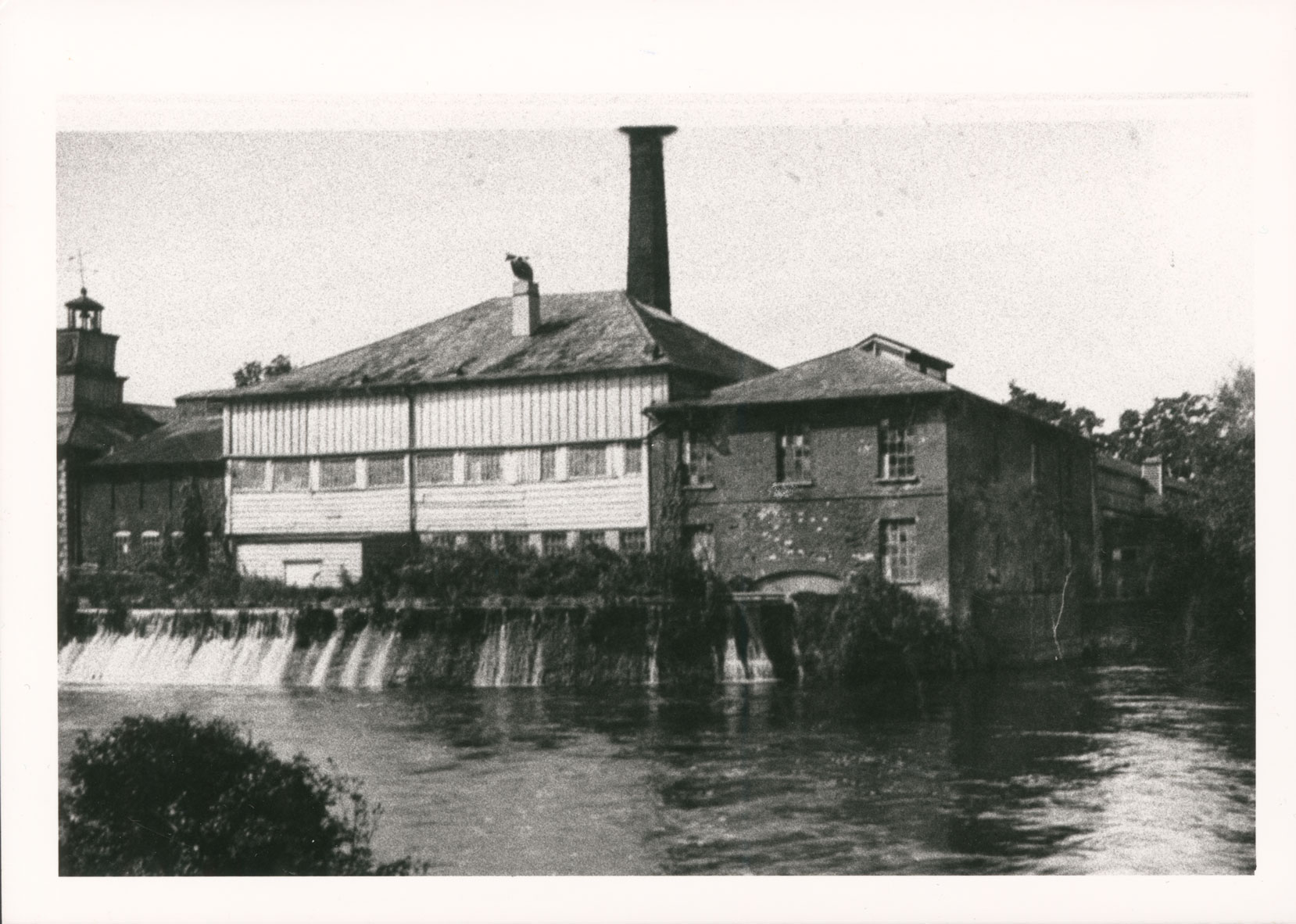 Black and white photograph of a paper mill from the outside surrounded by water.