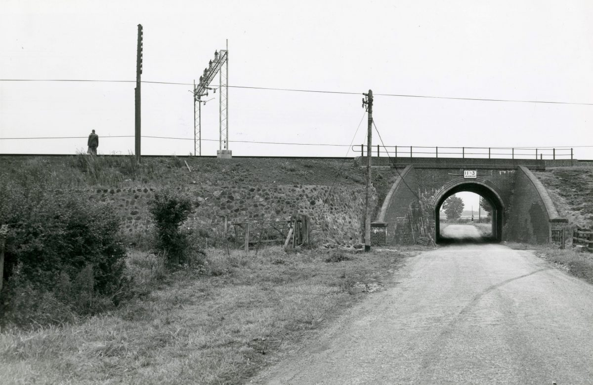 Black and white photograph of a railway line going over a road.