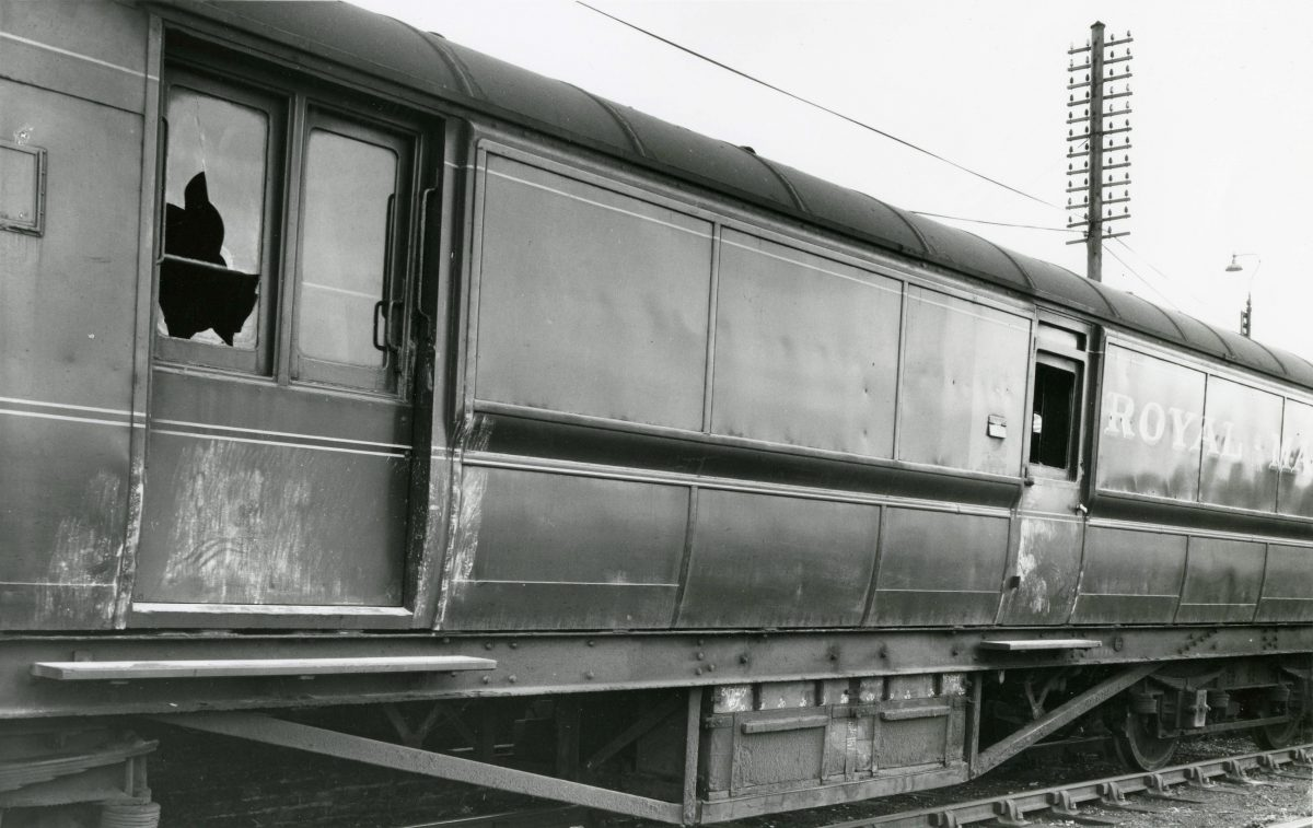 Black and white photograph of a Royal Mail train carriage with smashed windows.
