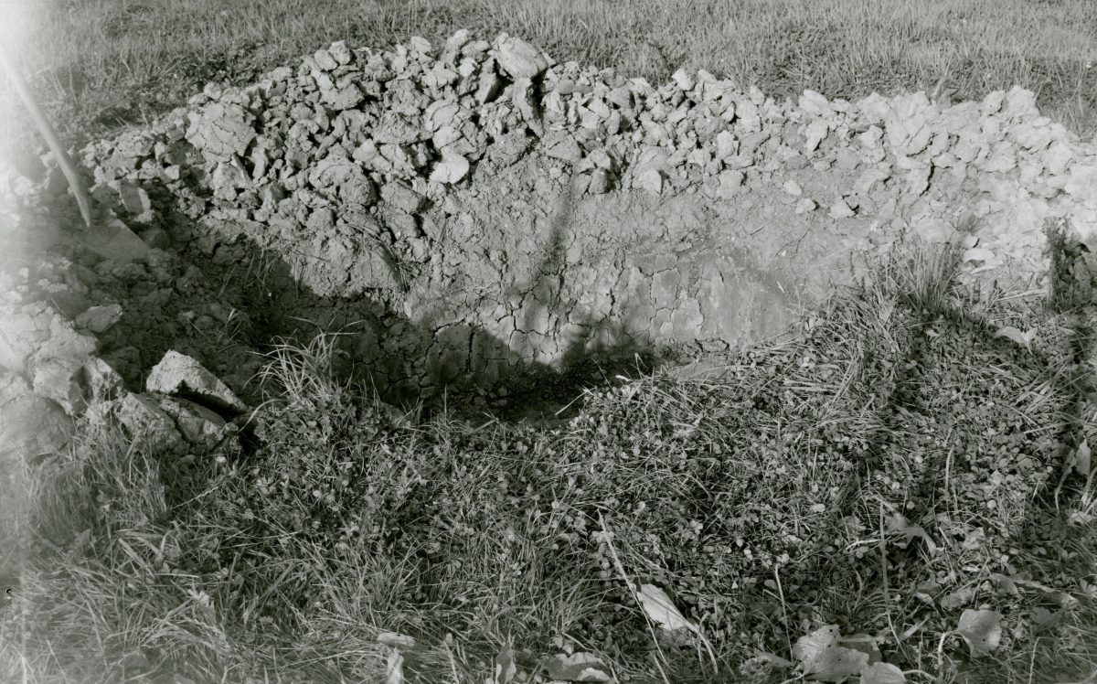 Black and white photograph of the pit dug next to the farm.