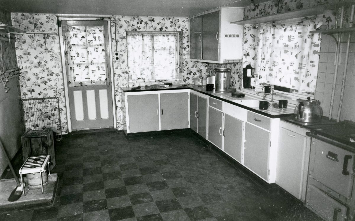 Black and white photograph from inside the farm kitchen.