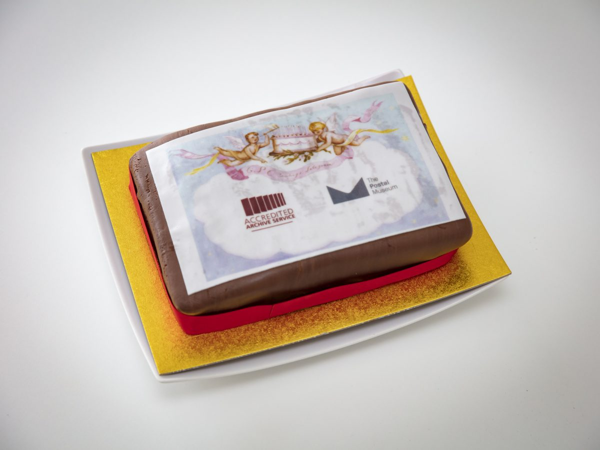 Rectangular cake with chocolate icing and an image of a greetings telegram. The telegram shows two cherubs carrying a cake. Also shows the Archive Service Accreditation and The Postal Museum logos