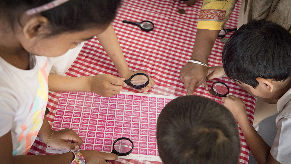An image of children bent over a sheet of stamps using magnifying glasses to get a closer look.