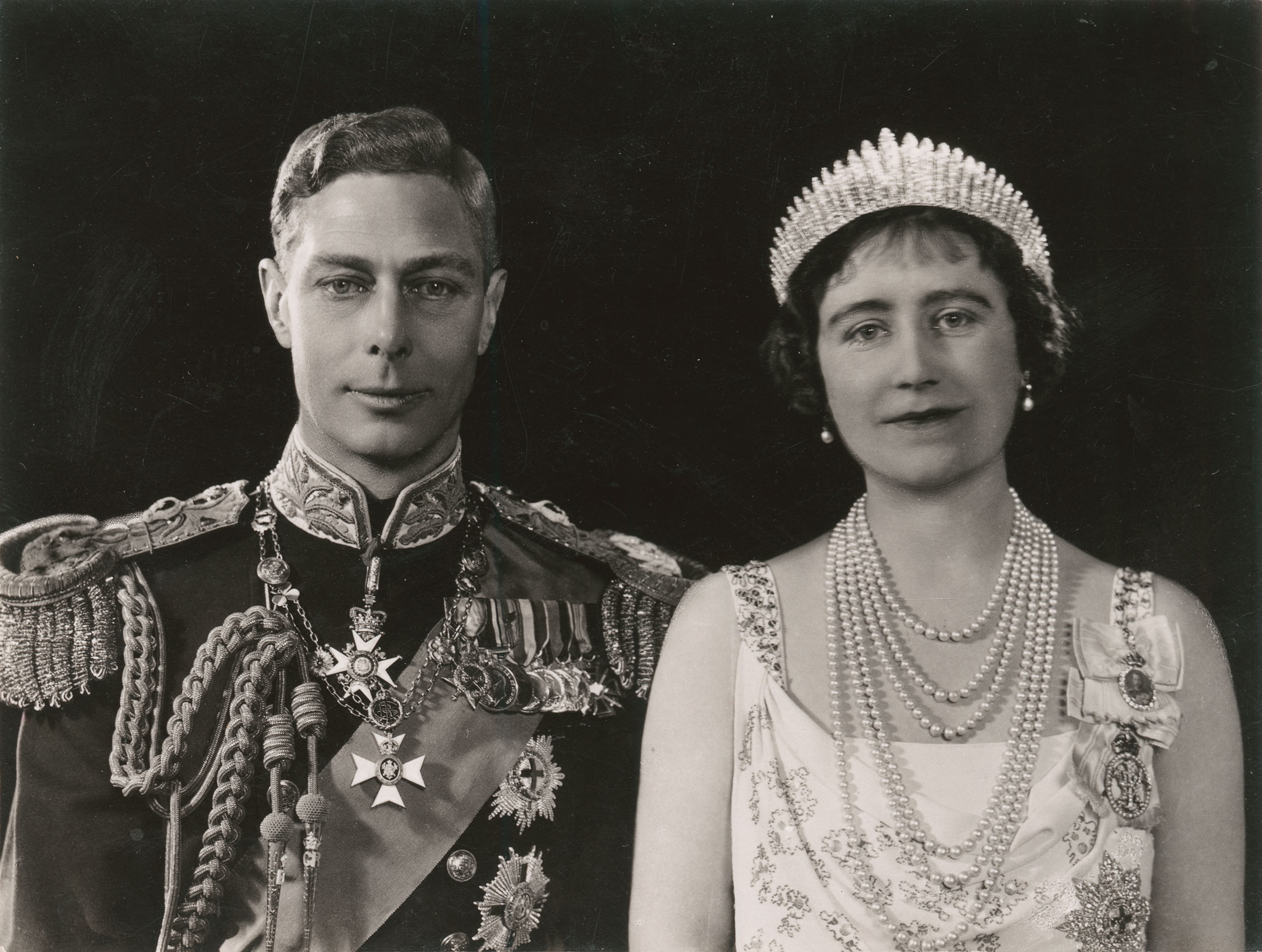 Black and white portrait of the couple side by side. The King wears medals and the Queen pearls and a tiara.