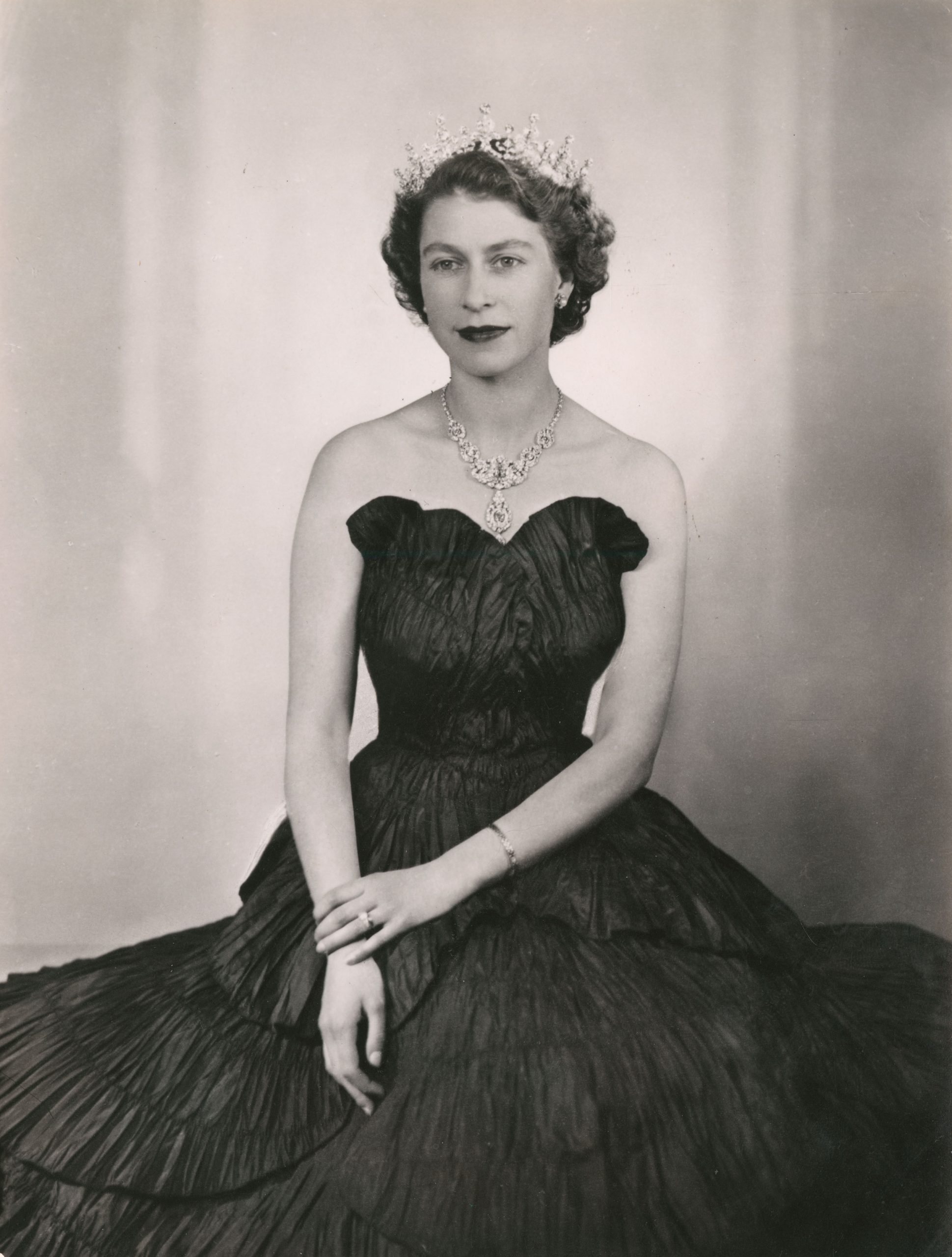 Black and white image of the Queen in a black ruffled dress wearing a tiara.
