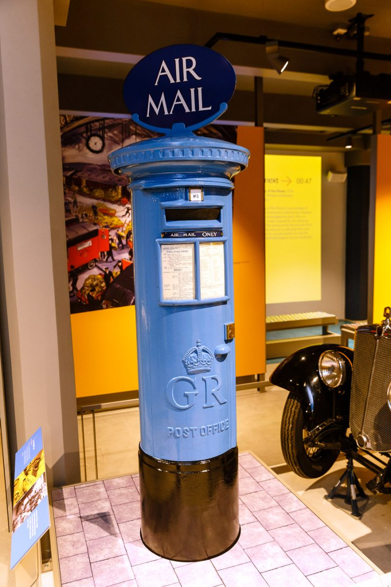 Photo of a blue airmail pillar box in the museum gallery space.
