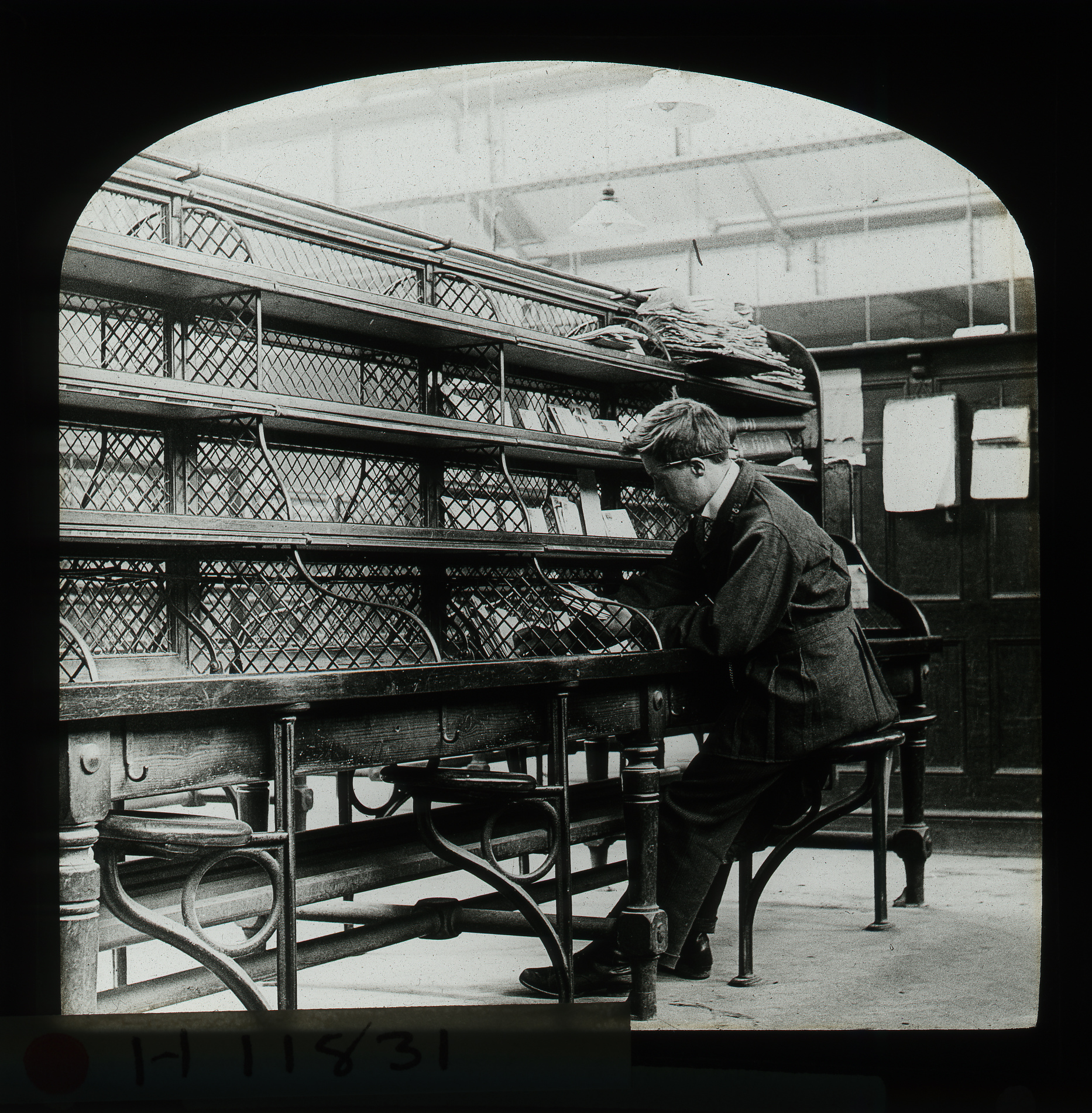 Black and white image of a men working at a desk with shelves above him.