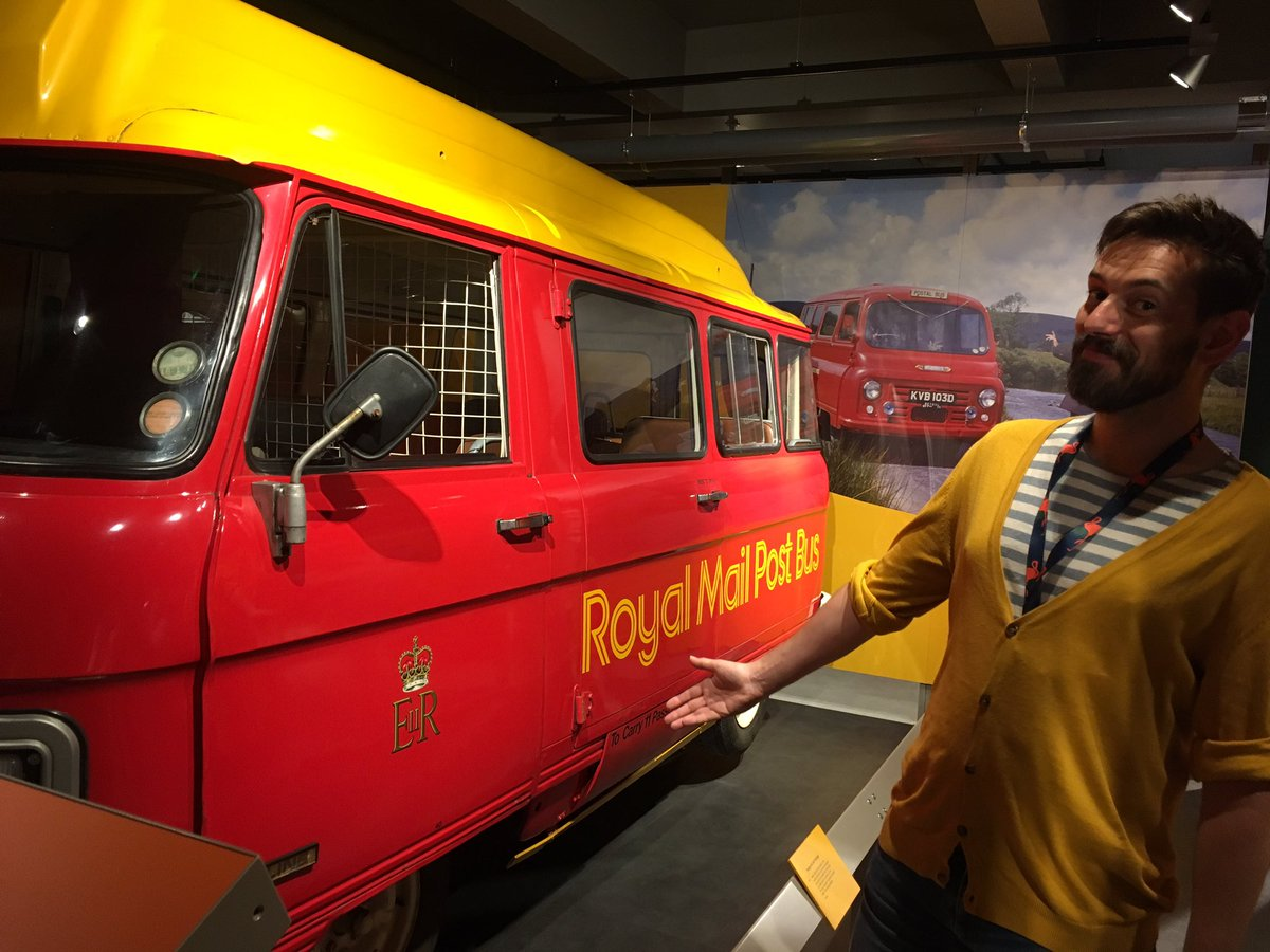 Tim Dunn stands by a post bus in The Postal Museum