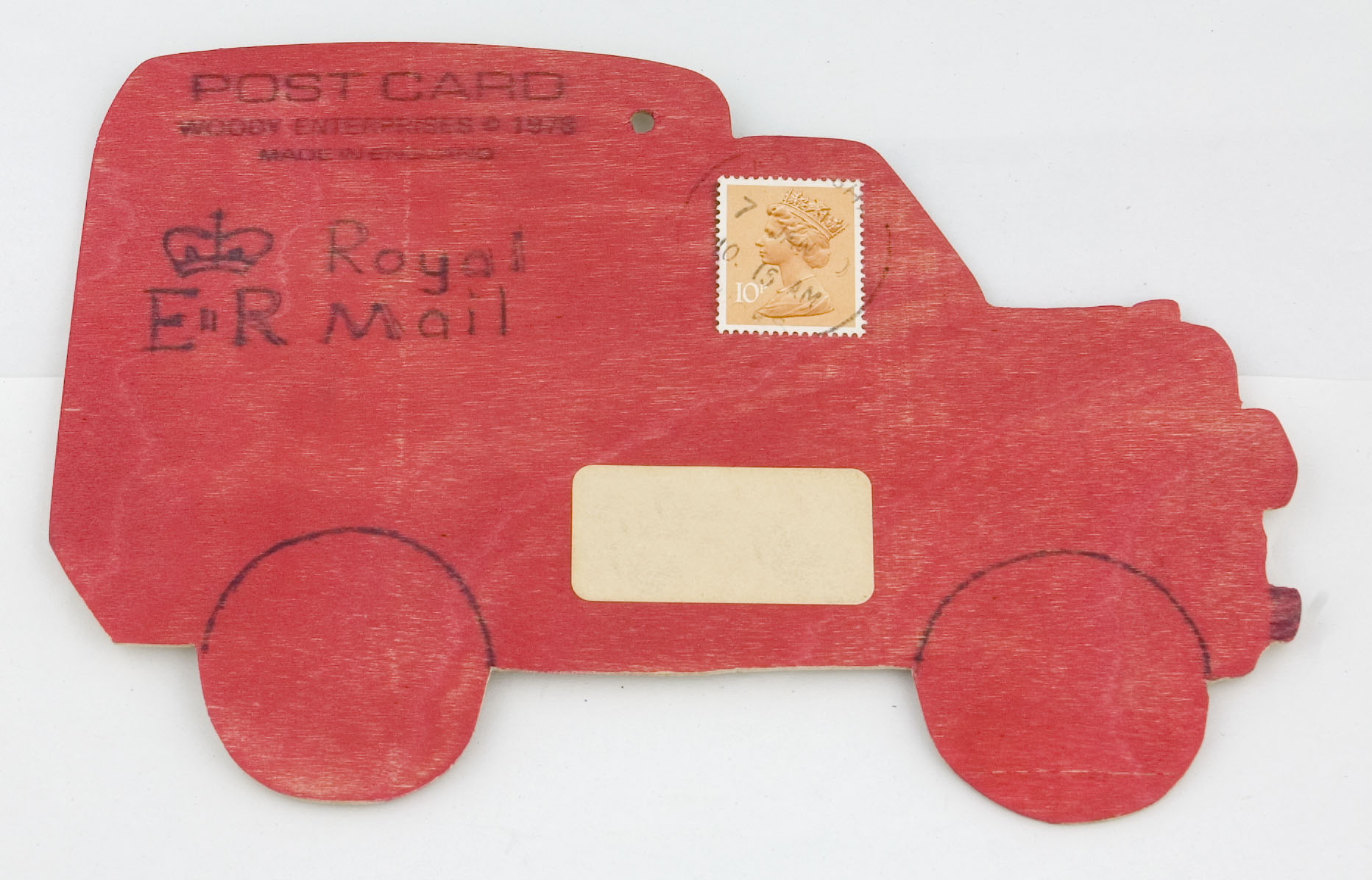 Image of a wooden postcard in the shape of a post van. The van is red with a hand drawn Royal Mail monogram.