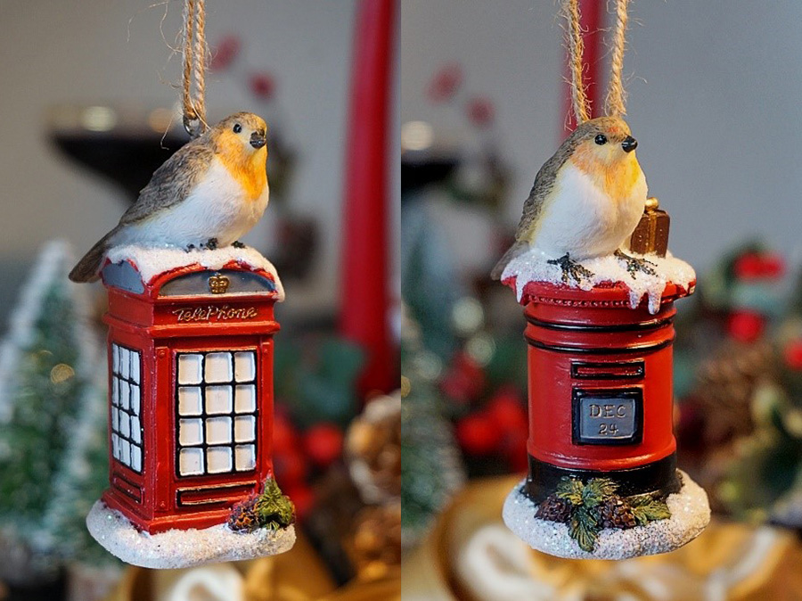 Photo showing two Christmas tree decorations with robins sitting on a letterbox and phonebox.