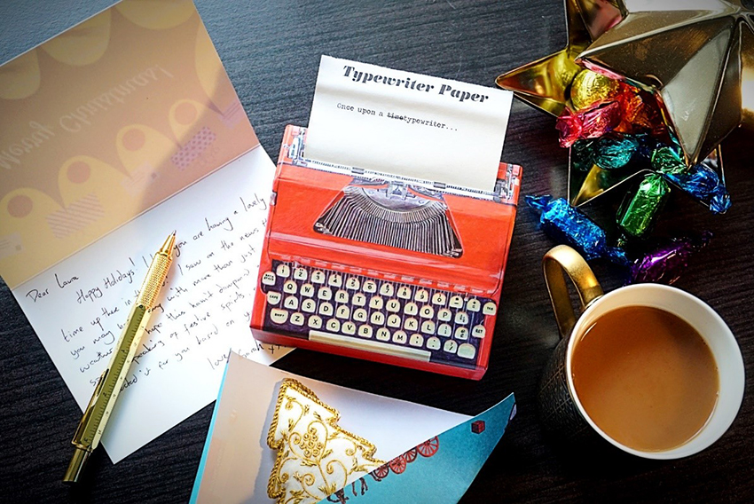 Photo showing a box with typewriter paper and other stationery on a desk.