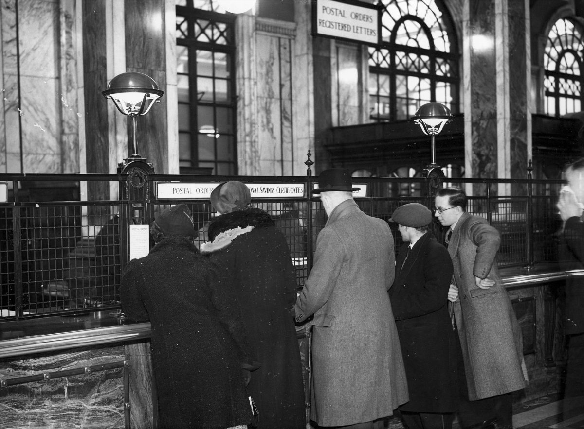 Black and white photograph of five people standing at a post office counter. The photograph is taken from behind the customers. The counter is wood with a metal divider. There is a sign with a white background and black text for postal orders and national savings certificates.