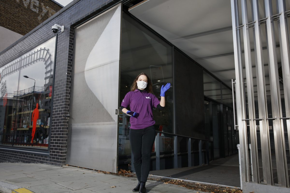 Visitor host stands outside The Postal Museum entrance