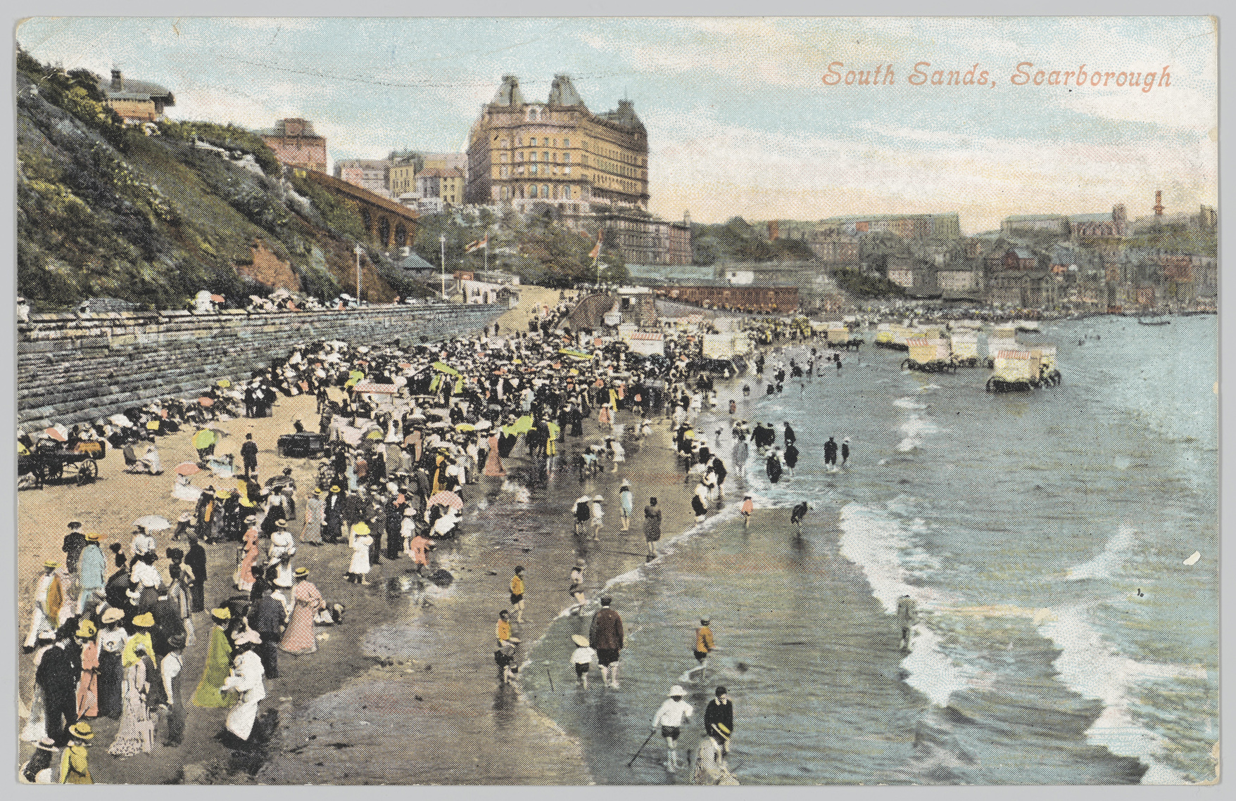 Postcard depicting many people on a beach with a large building in the background.
